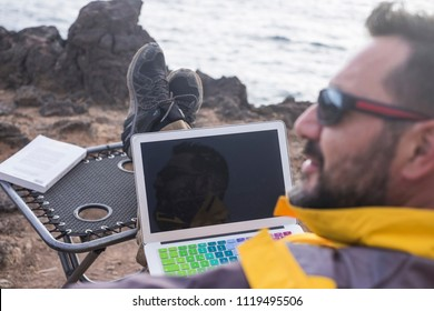 digital nomad at work in unusual office alternative open space on the coast sitting near the ocean waves. man in freedom activity far form cities and usual stressed lifestyle.