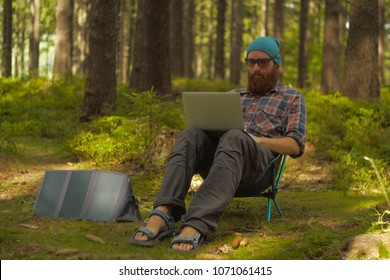 digital nomad, young caucasian man working on his laptop sitting on a camping chair in the woods, backpacking,