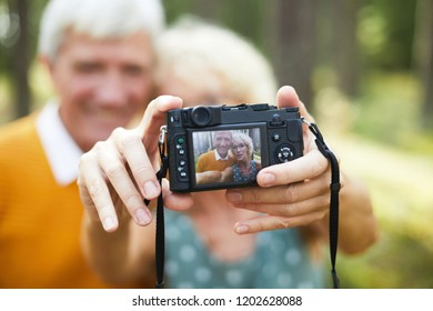 Digital photocamera in hands of senior female making shot of her husband and herself