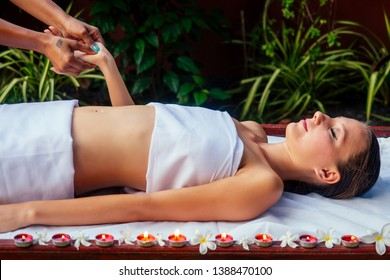 Digital pressure hands reflexology massage tuina therapy candles and flowers on the background