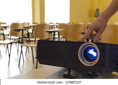 Digital projector being adjusted by a female hand
