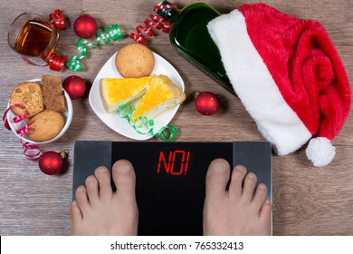 """Digital scales with male feet on them and sign """"no!"""" surrounded by Christmas decorations, sweets and bottle of alcohol. Shows how unhealthy lifestile during xmas holidays effects our body. Top view."""