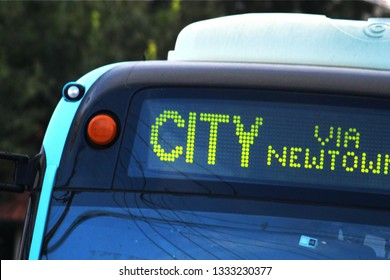 Digital signage on a public bus indicating it is going to the city