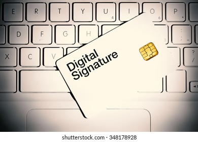 Digital Signature concept. Smart card on a keyboard of white laptop computer.