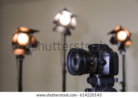 Digital SLR camera and three spotlights with Fresnel lenses. Manual interchangeable lens for filming. Shooting in the interior with artificial light. Equipment for movies.
