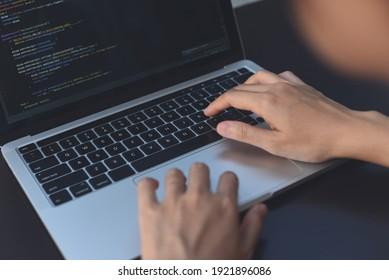 Digital software or application development, business technology concept. Programmer, man software developer coding HTML, programming Javascript on laptop computer screen, over shoulder view close up