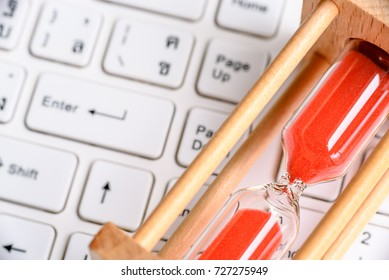Digital system time synchronization concept : Hourglass or sandglass and red beads with wood frame lies on a white desktop computer keyboard near an enter button.