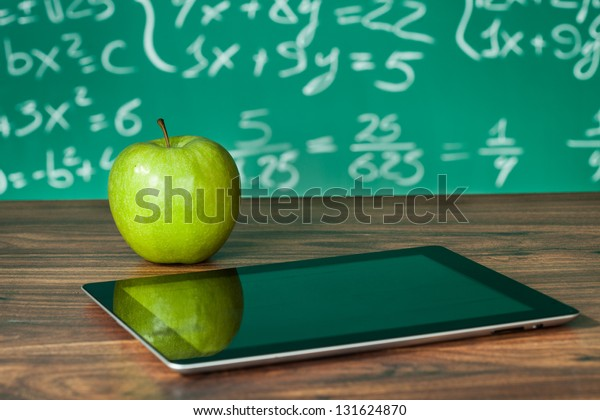 Digital tablet and apple on the desk in front of blackboard