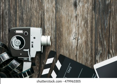 Digital tablet, clapper and filmstrip on a wooden desktop: cinema and entertainment concept