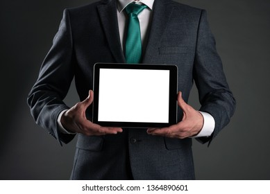 Digital tablet computer with a blank screen in a business man hands on gray background. Special offer mock up. Business proposal template. Contact us phone number background with copy space.