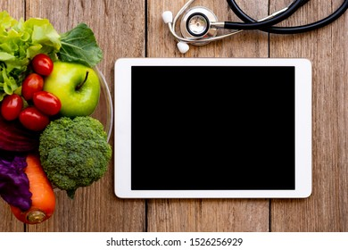 Digital tablet computer, medical stethoscope, mix raw vegetable, green apple fruit,tomatoes,orange carrot in glass bowl isolated on rustic wooden table background. Clipping path. Copy space for text..