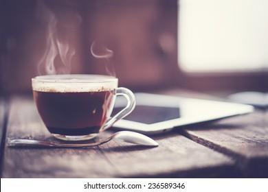Digitale Tablette und Tasse Kaffee auf dem alten Holzschreibtisch. Einfache Arbeitsfläche oder Kaffeepause morgens / selektiver Fokus