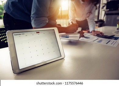 Digital tablet with deadline calendar remind on screen with businessman and partner working at background. tax season and debt collection concept.