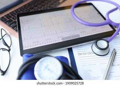 Digital tablet with electrocardiogram lying on doctors desk closeup. Ecg diagnosis of rhythm disturbances concept