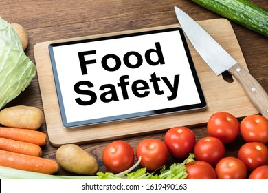 Digital Tablet With Food Safety Text Over Chopping Board Surrounded With Organic Fresh Vegetables