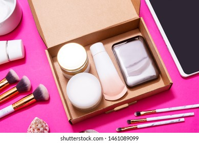Digital tablet and Makeup Subscription Boxes on pink table, top