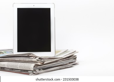 Digital tablet and newspapers, internet and electronic online news concept image