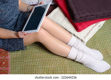 digital tablet on the legs of a young woman