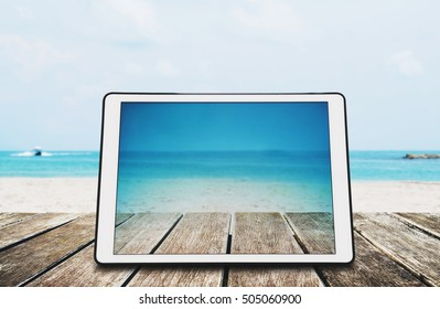 Digital Tablet on Wooden Desk at the Tropical Beach