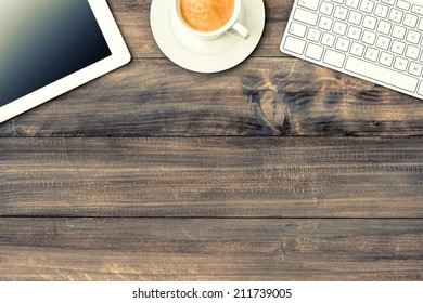 digital tablet pc, keyboard and cup of coffee on wooden table