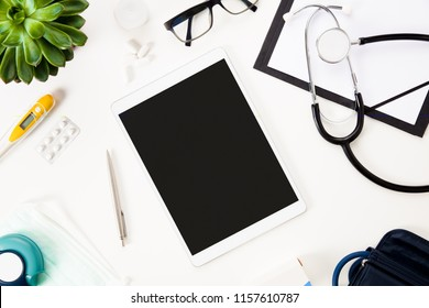 Digital Tablet With Pen And Medical Instruments On White Table