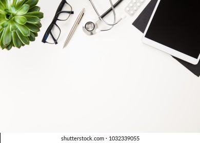 Digital Tablet With Stethoscope And Eyeglasses By Plant On Table
