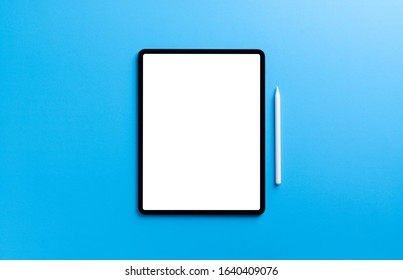digital tablet and stylus pen on light blue background