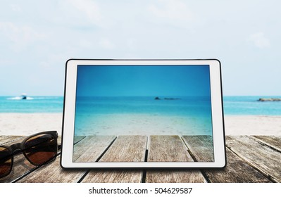 Digital Tablet with Sunglasses on Wooden Desk at the Tropical Beach