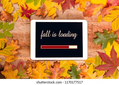 Digital tablet surrounded with autumn leaves, Fall is loading text on screen