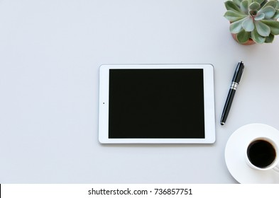 digital tablets computer white coffee cup,cactus on work table,top view,copy space for your text.