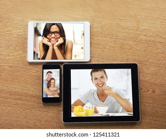 digital tablets and smart phone with images on a desktop. a mobile phone and a tablets with photos