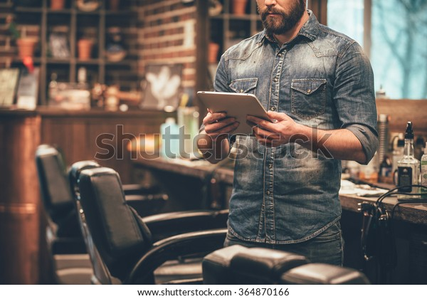 Digital technologies in any business. Close-up of young bearded man holding digital tablet while standing at barbershop