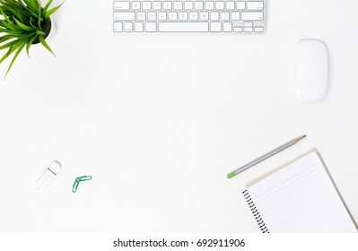 Digital Technology Composition flat Lay top View of white Office Desk with Keyboard Notepad Pencil and green Flower