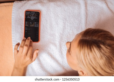 Digital technology. Nice pleasant woman using her new smartphone while being in the spa salon