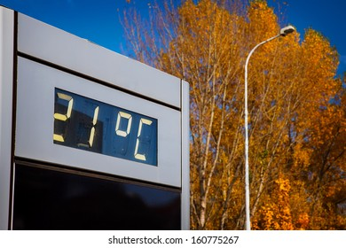 Digital thermometer with 21 degrees Celsius in front of yellow treetops in the autumn.