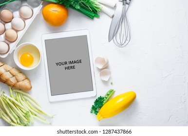 Digital touch screen tablet with fresh vegetables and kitchen utensils on background, top view