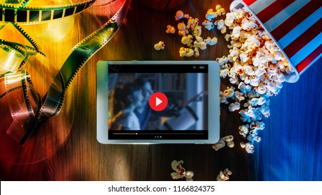 Digital touch screen tablet with popcorn and filmstrip; movie online streaming cinema and entertainment concept
