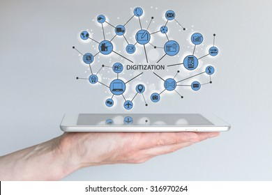 Digitization and digital disruption concept. Male hand holding modern tablet or smart phone with illustration of connected devices and information.