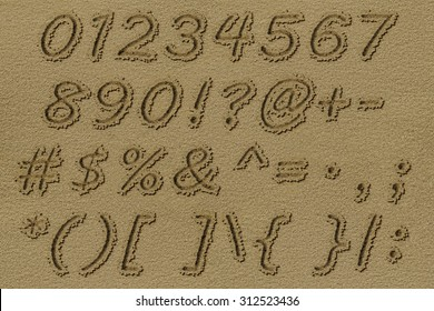 Digits & signs written on a beach sand