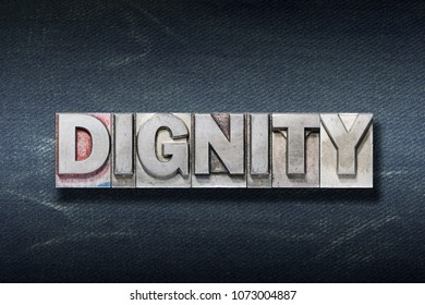 dignity word made from metallic letterpress on dark jeans background