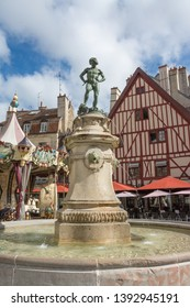 DIJON, BURGUNDY, FRANCE - SEPTEMBER 24, 2018: Fountain with winemaker statue in The Francois-Rude Square in Dijon, Burgundy, France. The statue it is the work of Noël-Jules Girard