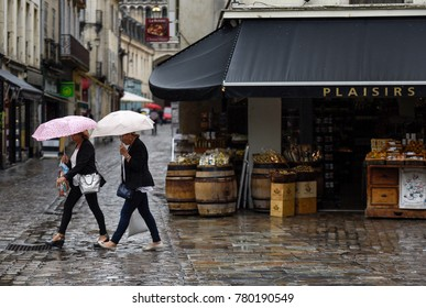 Dijon, France - 05.15.2015: Two women under umbrellas go shopping on rainy Dijon Street