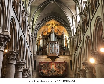 DIJON, FRANCE - APRIL 22, 2018: The organ of the Notre Dame Cathedral in Dijon, France is located over a large tapestry at the back of the main hall
