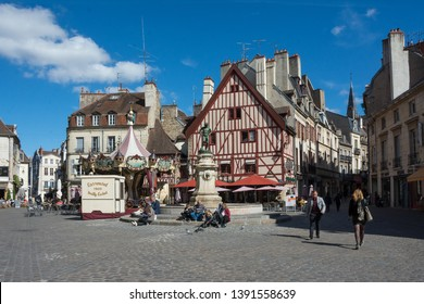 DIJON, FRANCE - SEPTEMBER 24, 2018: The Francois-Rude Square and the fountain with winemaker statue and with a carousel in Dijon, Burgundy, France. The statue it is the work of Noël-Jules Girard
