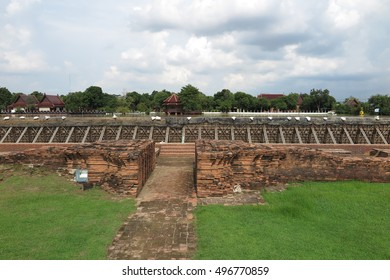 Dike, long wall or embankment built to prevent flooding at river near Wat Chaiwatthanaram, Ayutthaya historical park, Thailand