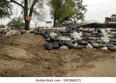 Dikes or embankment built to prevent flooding from the river. Sandbags for flood defense . Sacks with sand to prevent a flood. Dangerous increase of water from rain storm. Dike keeps from flooding.