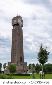 Diksmuide, Flanders, Belgium -  June 19, 2019: IJzertoren, tallest peace monument of WW 1 against gray blue cloudscape. Dutch words saying No More War. Some green foliage and lawn.