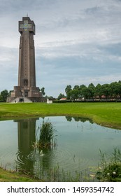 Diksmuide, Flanders, Belgium -  June 19, 2019: IJzertoren, tallest peace monument of WW 1 against gray blue cloudscape. On wall saying No More War. Reflection in pond. Some green foliage and lawn.