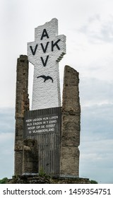 Diksmuide, Flanders, Belgium -  June 19, 2019: Closeup of Black on White Crypt memorial, remnants of dynamited tower, at site of IJzertoren, tallest peace monument of WW 1 against gray cloudscape.