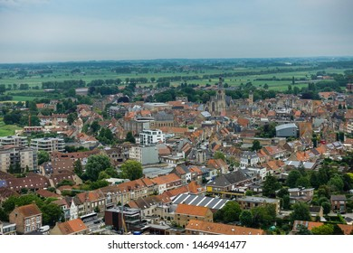 Diksmuide, Flanders, Belgium -  June 19, 2019: View on dowtown from up IJzertoren, tallest peace monument of WW 1. Brick buildings with red roofs, towers of church and city hall, green pasture.